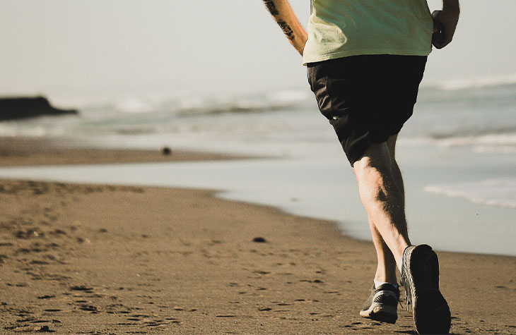 Man Running On Beach To Show How Physical Fitness Can Affect Addiction Treatment