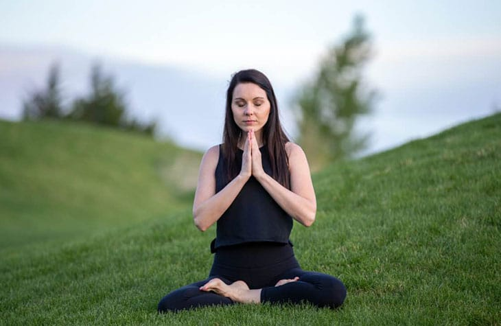 Woman Meditation In Grass Field As Part Of Her Mindfulness And Addiction Recovery Treatment