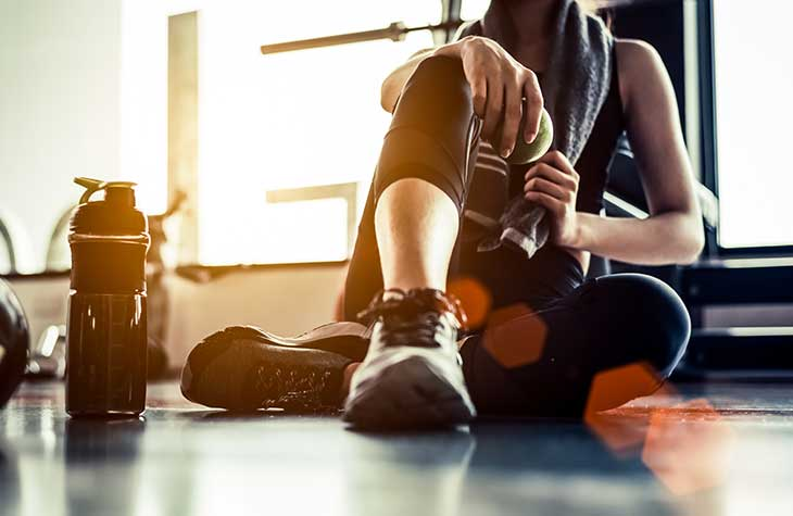 Woman Sitting On Floor After Exercising To Help With Alcohol Recovery