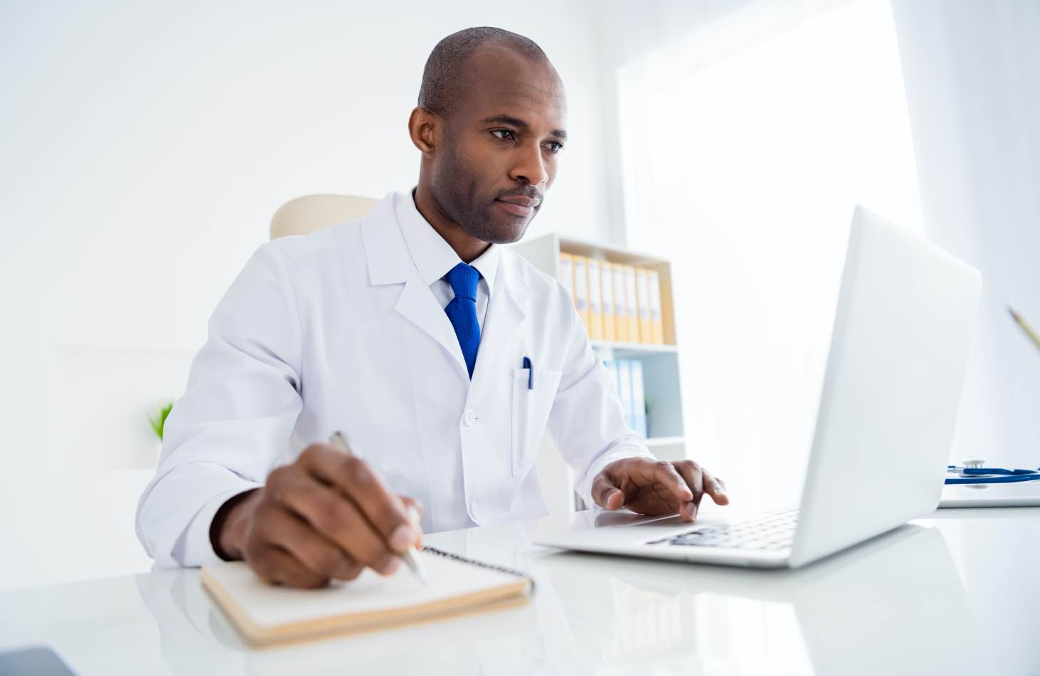 A Doctor On His Laptop Looking Up Medication Assisted Treatment Options For A Client