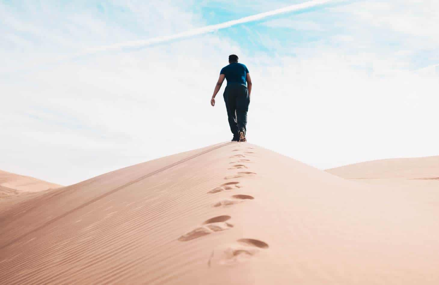 A Man Walking In A Desert Representing The Journey Of Sobriety And Medication Assisted Treatment