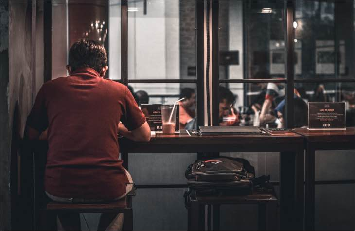 Person Sitting At Bar Struggling With An Alcohol Addiction