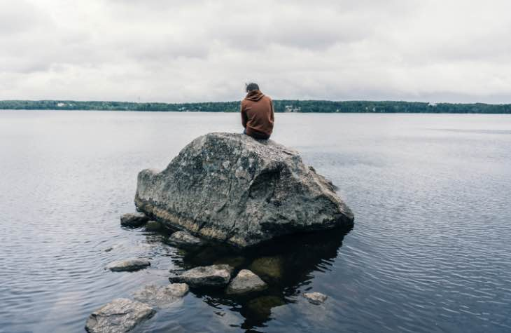 Person Sitting On Rock Symbolizing The Lonliness People Feel Prior To Addiction Treatment