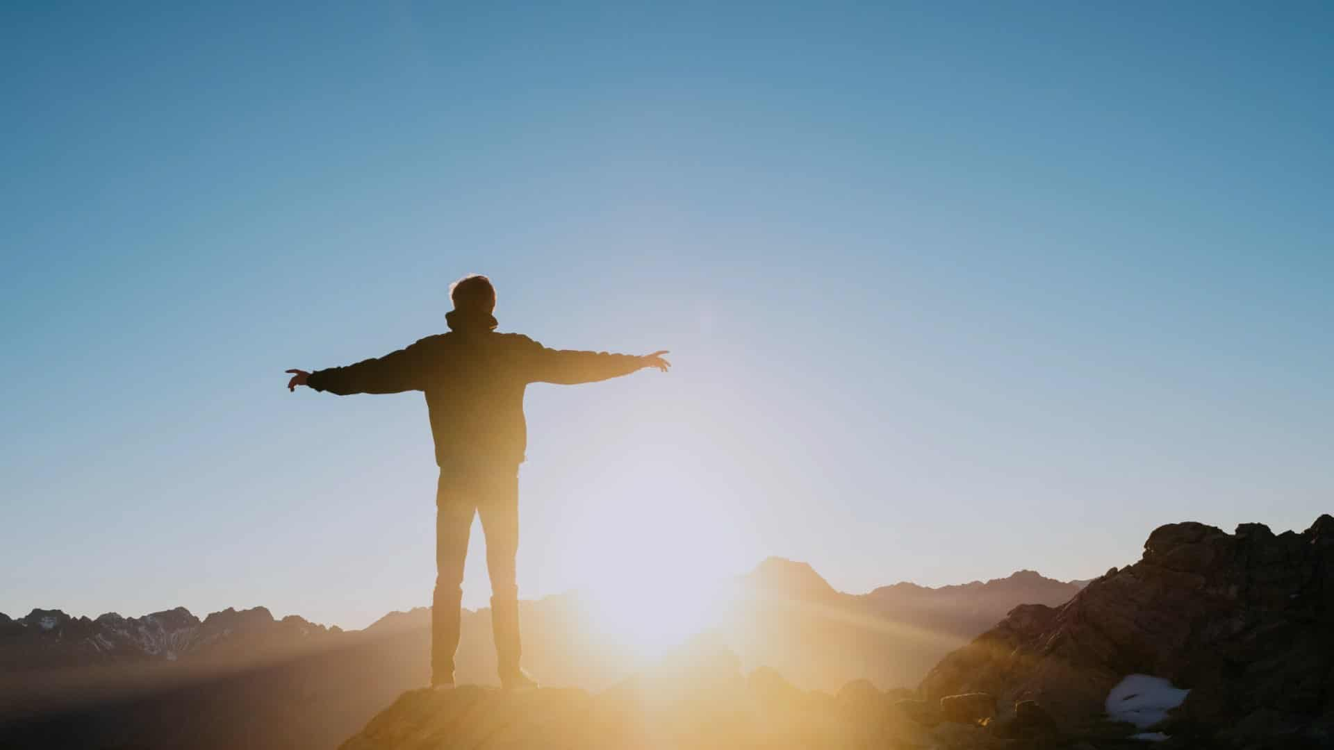 Young Man Atop Mountain Facing Sun Rise On Does Rehab Work Blog