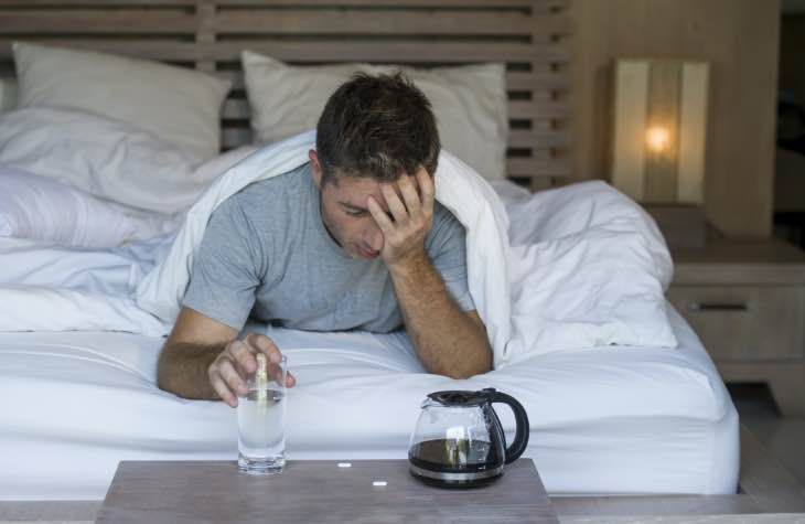 Man In Bed Exhibiting The Short Term Mental Effects Of Alcohol Abuse