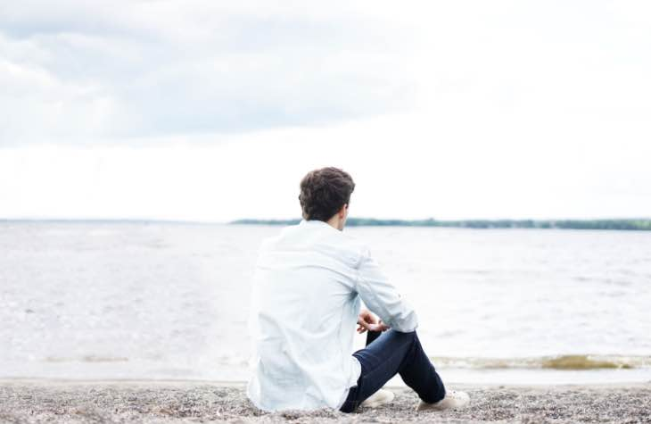 Person Sitting On Beach Focused On Long Term Sobriety From Alcohol Addiction