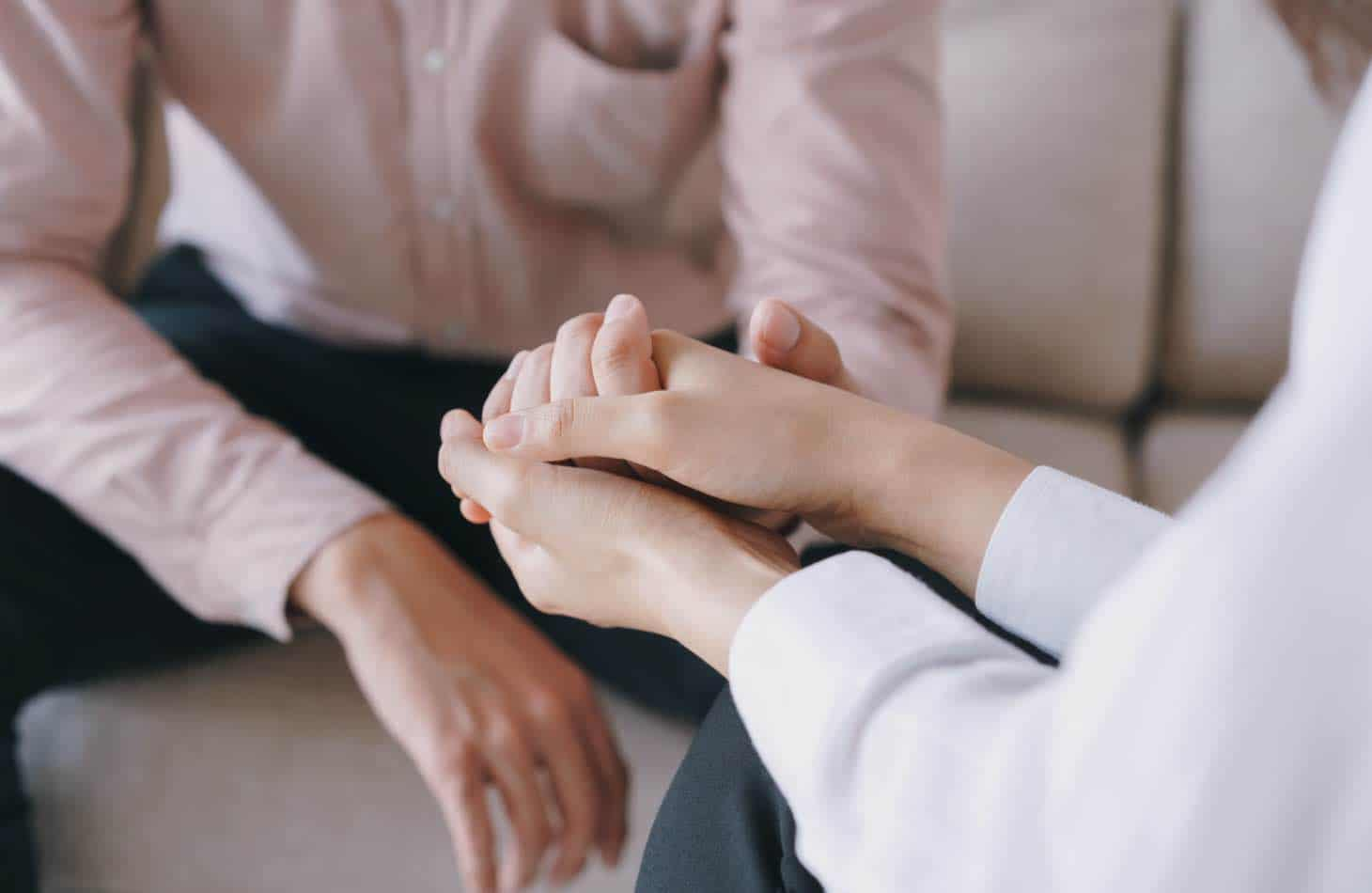 Therapist Holding Hand Of Client Dealing With Dual Diagnosis And Alcohol Addiction
