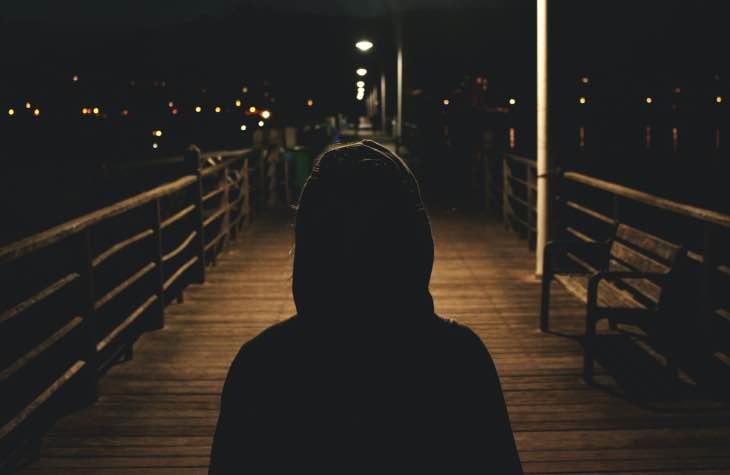 Person on dark bridge experiencing initial symptoms from detox