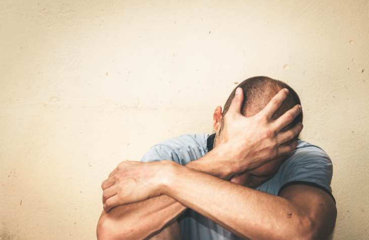 Man With Hand On Head Experiencing Opioid Withdrawal