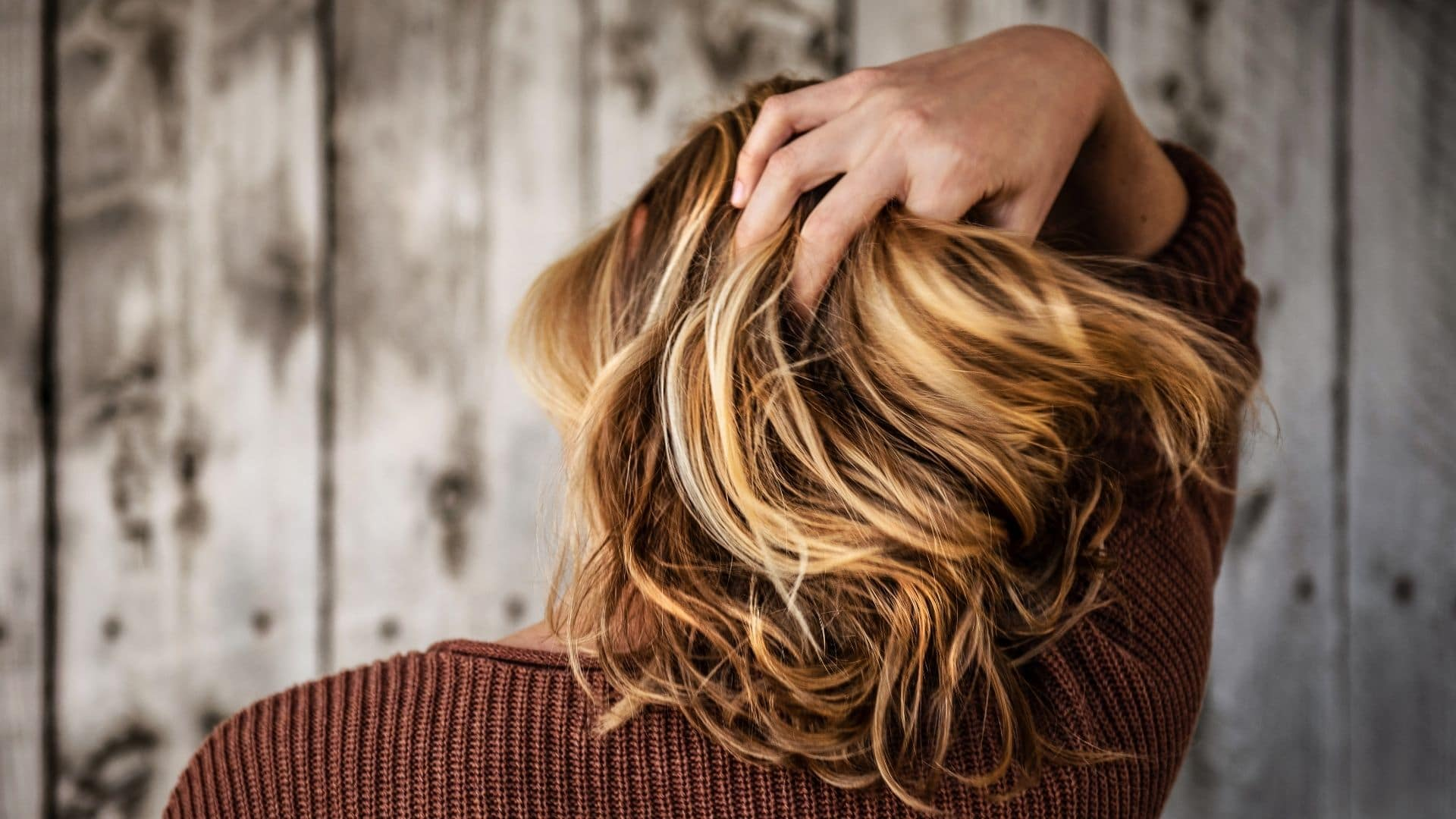 woman running fingers through hair wondering which illegal drugs that cause hair loss
